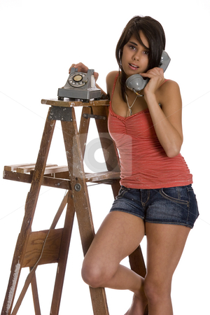 Talking on the phone stock photo, Teenage girl standing on ladder talking on a old rotary phone by Yann Poirier