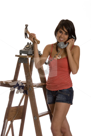 Renovation advice stock photo, Teenage girl standing on ladder talking old rotary phone with a hammer in her hand by Yann Poirier