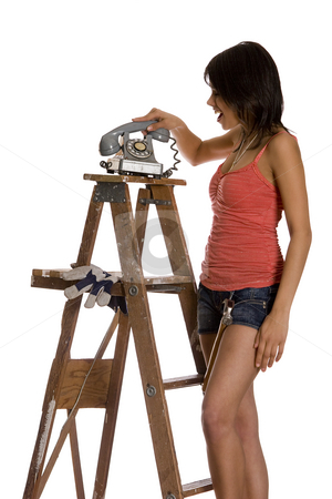 Slamming phone stock photo, Teenage girl standing on ladder slamming an old rotary phone by Yann Poirier