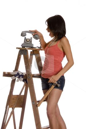 Slamming phone stock photo, Teenage girl standing on ladder slamming an old rotary phone by Yann Poirier