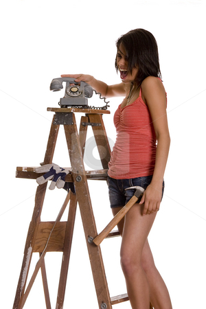 Slamming phone stock photo, Teenage girl standing on ladder screaming while slamming an old rotary phone by Yann Poirier