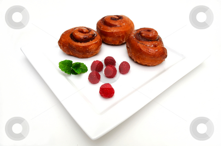 Cinnamon Roll stock photo, Cinnamon buns and fresh red Raspberries on a square white plate isolated on white by Lynn Bendickson