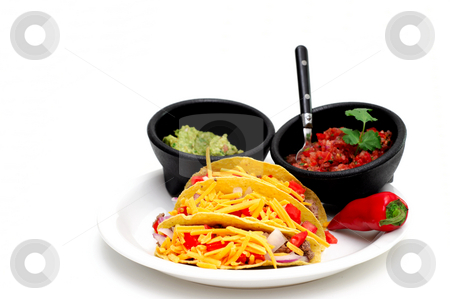 Hard Shell Taco stock photo, Three hard shell tacos on a white plate with sides of tomato and chili salsa and fresh guacamole isolated on a light colored background by Lynn Bendickson