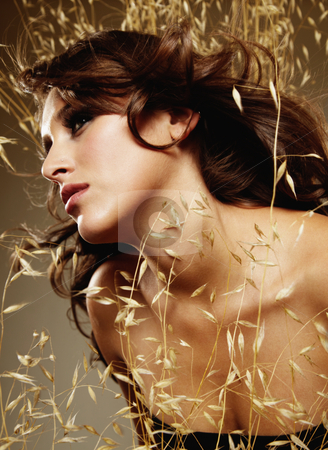 Woman Surrounded by Wheat stock photo, Young woman surrounded by wheat. Vertically framed shot. by Media Deva