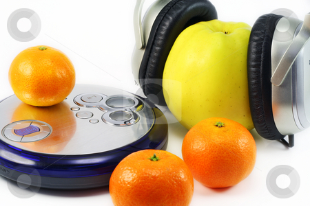 Fruit listens to music stock photo, Juicy ripe tangerines and huge yellow apple listen to music through compact player. by Aleksandr Volokov