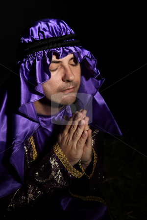 Worshipping man stock photo, Man arrayed in purple and gold robe with hands together praying by Leah-Anne Thompson