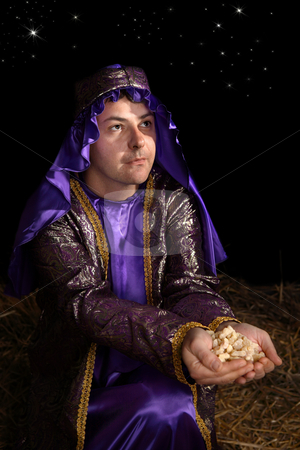 Wiseman bearing gift of frankincense stock photo, Wise man arrayed in majestic purple robe woven with gold metallic thread is offering in his palms finest pure frankincense. Focus to face. by Leah-Anne Thompson
