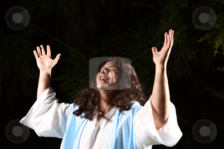 Praise the Lord stock photo, A man dressed in robe hands raised in the air praising or worshipping God on a dark background. by Leah-Anne Thompson