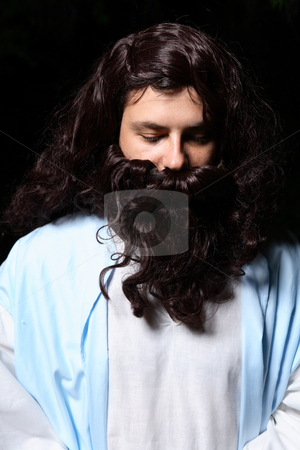 Man praying at night stock photo, Man with head solemnly bowed praying at night. by Leah-Anne Thompson