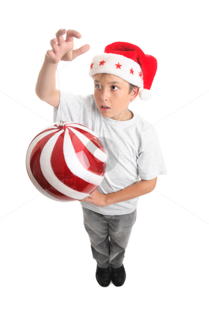 Boy and Christmas Bauble stock photo, A boy standing is spinning or hanging a large Christmas bauble.    Bauble shows some motion. by Leah-Anne Thompson