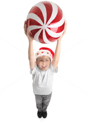 Celebrate Christmas Big Way stock photo, A smiling boy holding a large Christmas bauble in two hands above his head. by Leah-Anne Thompson