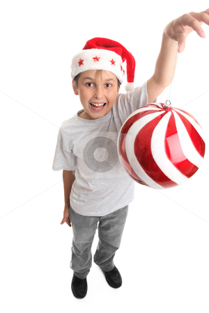 Putting up the Christmas ornaments stock photo, Childs arm stretched up high with a large bauble dangling from fingers by Leah-Anne Thompson