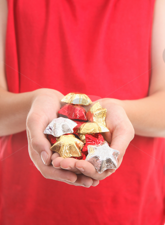 Handful of chocolates stock photo, Cupped hands hold a handful of  foil wrapped chocolate stars. by Leah-Anne Thompson