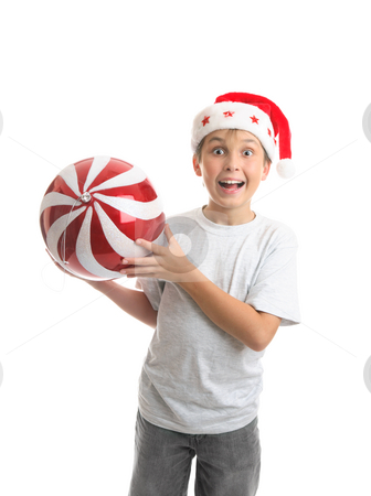 Child boy holding Christmas bauble decoration stock photo, An excited ecstatic boy holding a big Christmas bauble ball decoration.  Red and white with sparkling glitter and a silver thread by Leah-Anne Thompson