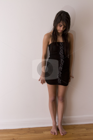 Barefoot teen stock photo, Teenager girl in little black dress standing barefoot against a wall by Yann Poirier