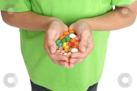 Hands holding lollies stock photo, Child's hands holding a handful of lollies. by Leah-Anne Thompson