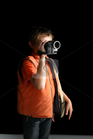 Creating a home movie stock photo, A child standing in a room or studio using a handheld digital video camera by Leah-Anne Thompson