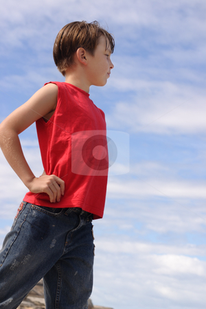 Boy against blue cloudy sky stock photo, A boy stands hands on hips against a blue sky by Leah-Anne Thompson
