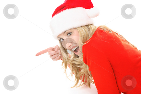 Christmas girl pointing to your message or product. stock photo, A surprised or delighted female wearing a festive santa hat points to your Christmas message, slogan or product. by Leah-Anne Thompson