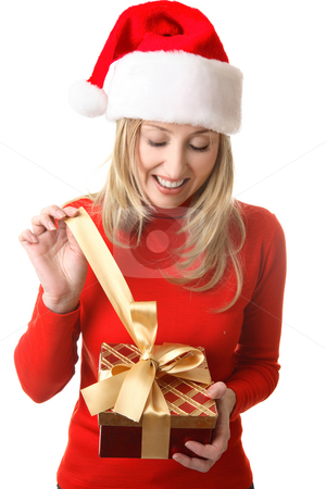 Female opening a present stock photo, A happy girl in anticipation,  pulls open the golden ribbon bow from a Christmas present by Leah-Anne Thompson