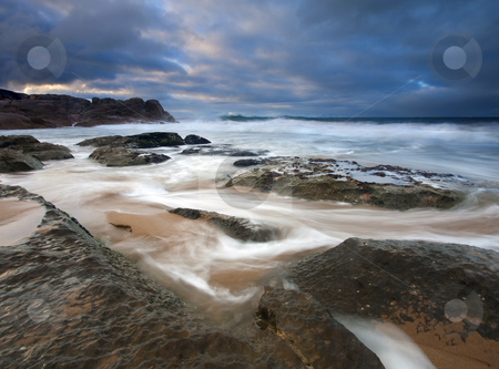 Through the Fissures stock photo, Ebbing Tides feed through the fissures in the rocks on Knight's Beach at sunrise. by Mike Dawson