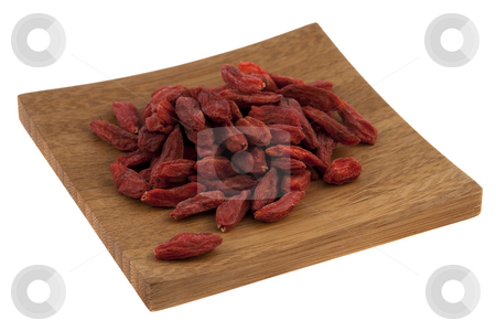Dried Tibetan goji berries (wolfberry)  stock photo, A pile of dried Tibetan goji berries (wolfberry) on a small wooden square tray isolated on white, selected focus on fruits by Marek Uliasz