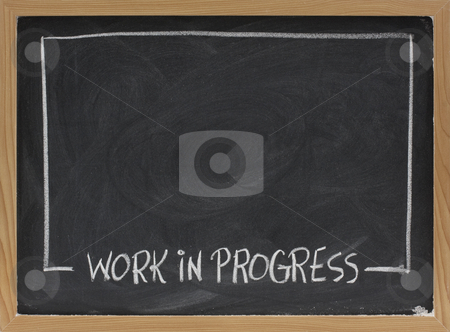 Work in progress on blackboard stock photo, Work in progress text in white chalk handwriting, rectangular frame on blackboard with eraser smudge patterns and blank copy space by Marek Uliasz