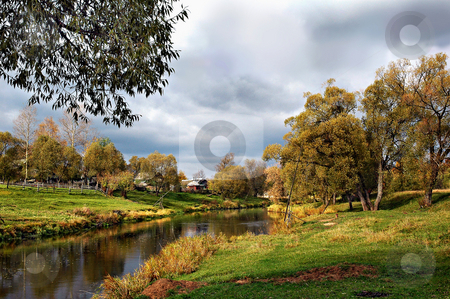 Autumn in the village stock photo, The village on the banks of a small river in a quiet golden autumn day by Olga Drozdova