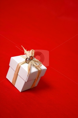 Gift box presentt tied with raffia stock photo, A white gift box tied with raffia and decorated with beads sits on a red background.  Suitable for birthday, Christmas, valentine,  or other special occasions. by Leah-Anne Thompson