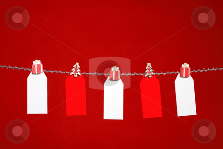 Tags on red background stock photo, Festive red and white tags hanging from silver tinsel  line on a red background by Leah-Anne Thompson