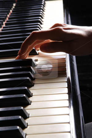 Woman playing piano stock photo, A  young woman playing piano closeup by Remy Musser
