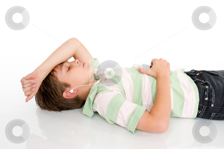 Boy listening music stock photo, A young boy lying down listening to music on a digital portable mp3 player. by Leah-Anne Thompson