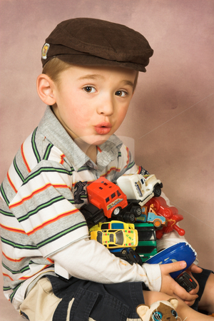 All Mine stock photo, Young boy with all his toy cars in his arms by Carla Booysen