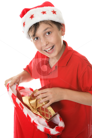 Child with a sack of presents stock photo, A jovial, child takes presents out at Christmas by Leah-Anne Thompson