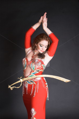 Belly Dancer balancing sword stock photo, Belly Dancer in red costume balancing a tribal sword by Carla Booysen