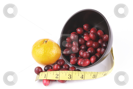Cranberries spilling out of a Black Bowl with Tape Measure  stock photo, Red ripe cranberries spilling out of a small round black bowl on its side with a tape measure and satsuma on a reflective white background by Keith Wilson