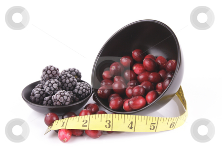 Cranberries spilling out of a Black Bowl with Frozen Blackberrie stock photo, Red ripe cranberries spilling out of a small round black bowl on its side with a tape measure and frozen blackberries on a reflective white background by Keith Wilson