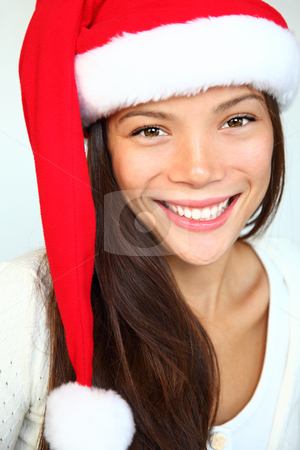 Christmas girl stock photo, Christmas girl in a Santa hat smiling. Very beautiful mixed asian / caucasian model. Isolated on white background. by Maridav