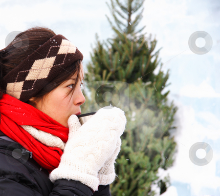 Winter hot drink stock photo, Woman drinking hot coffee or tea outdoors in winter. The background is an ice wall. by Maridav
