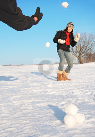 Winter fun - snowball fight stock photo, Snowball fight - winter fun. Couple throwing snowballs at each other. by Maridav