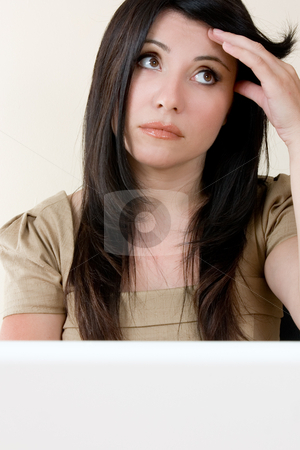 Stressed working woman stock photo, Working woman looking a little worried or stressed. by Leah-Anne Thompson