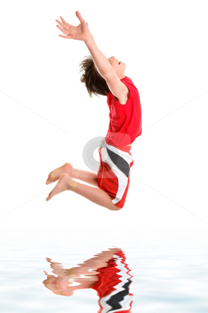 Leaping child hands stretched to sky stock photo, A happy boy leaps mid jump with hands stretched towards the sky. by Leah-Anne Thompson