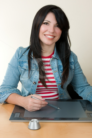 Woman using a graphic tablet and pen stock photo, A smiling woman sitting at desk using a graphic tablet by Leah-Anne Thompson