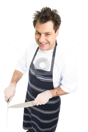 Smiling butcher or chef sharpens knife stock photo, A friendly butcher or chef sharpens a knife. by Leah-Anne Thompson