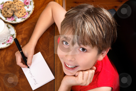 Child writing  a letter or card at Christmas stock photo, A child sitting at a desk writing a letter for Santa or Christmas card. by Leah-Anne Thompson