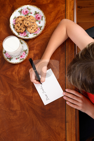 Child writing a letter stock photo, A child at desk writing a letter to Santa Claus, beside him a plate of choc chip cookies and glass of milk. by Leah-Anne Thompson