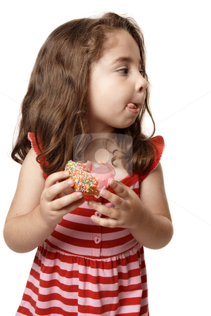 Little girl tasty sweet doughnut stock photo, A little girl enjoys a sweet pink iced doughnut.   She is licking her lips and looking sideways.  Suitable for copy. by Leah-Anne Thompson
