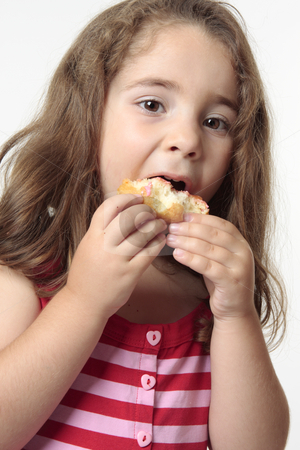 Child eating junk food donut. stock photo, Young child talking a big bite from a doughnut. by Leah-Anne Thompson