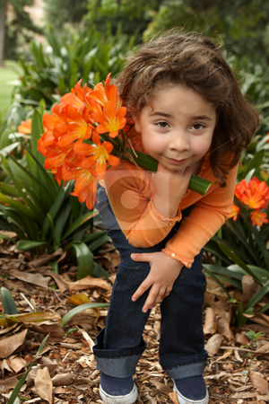 Young girl with a bunch of lilies stock photo, Little girl holding a bunch (umbels) of lilies  (clivia miniata).  She is wearing navy jeans and an orange twin set and  standing in the garden bed. by Leah-Anne Thompson