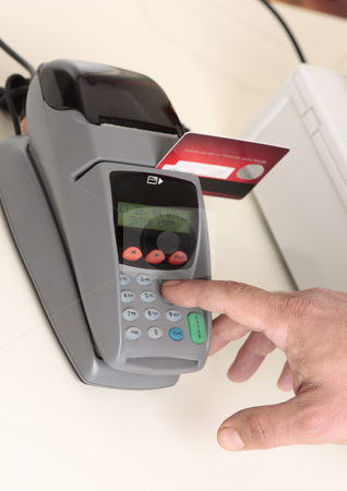 Credit or debit card transaction stock photo, A retailer, salesman or customer using an eft pos machine to make a transaction payment.  Focus to hand and machine only. by Leah-Anne Thompson